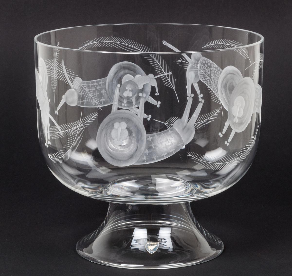 Skål på fot, kristall. Orrefors glasbruk, desing Gunnar Cyrén. Cylindrisk med välvd botten. Konkav fot. Graverad dekor av lejon och apor. På foten grå sköldformad etikett med i vitt orre och texten : ORREFORS SWEDEN.