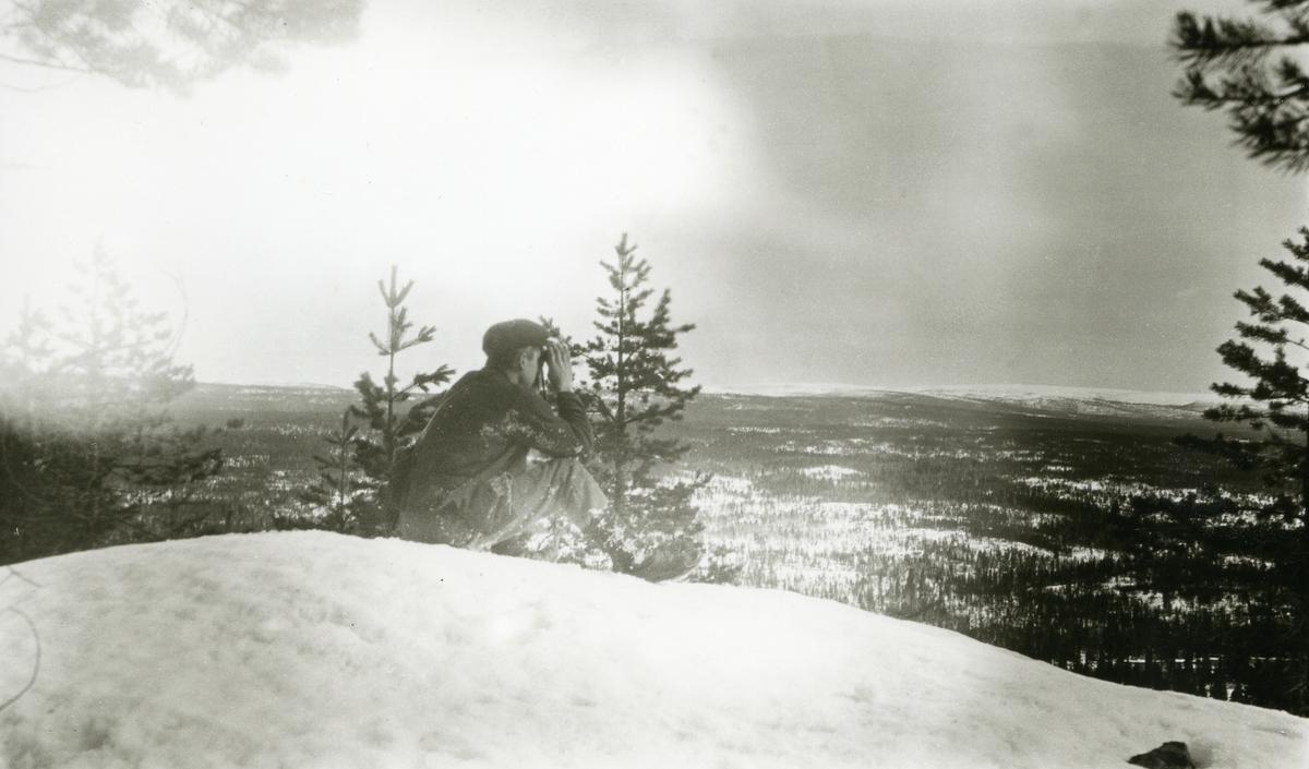 Mann med kikkert sittende på Buskneshøgda, Galåsen, og speider utover mot grensefjellranda i horisonten.