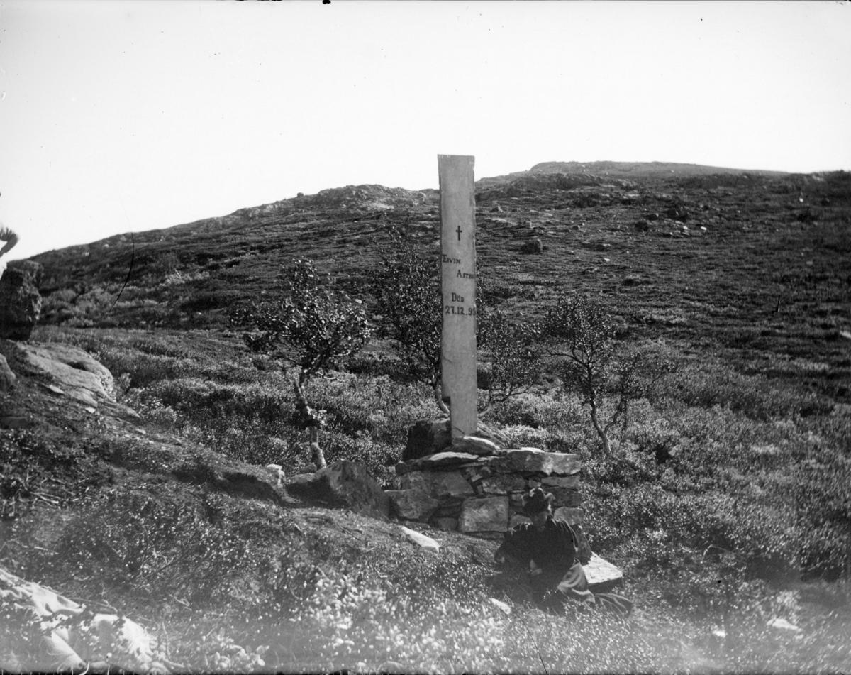 Astrupstøtten ved Hjerkinnpå Dovrefjell. Sittende kvinne foran støtten.
