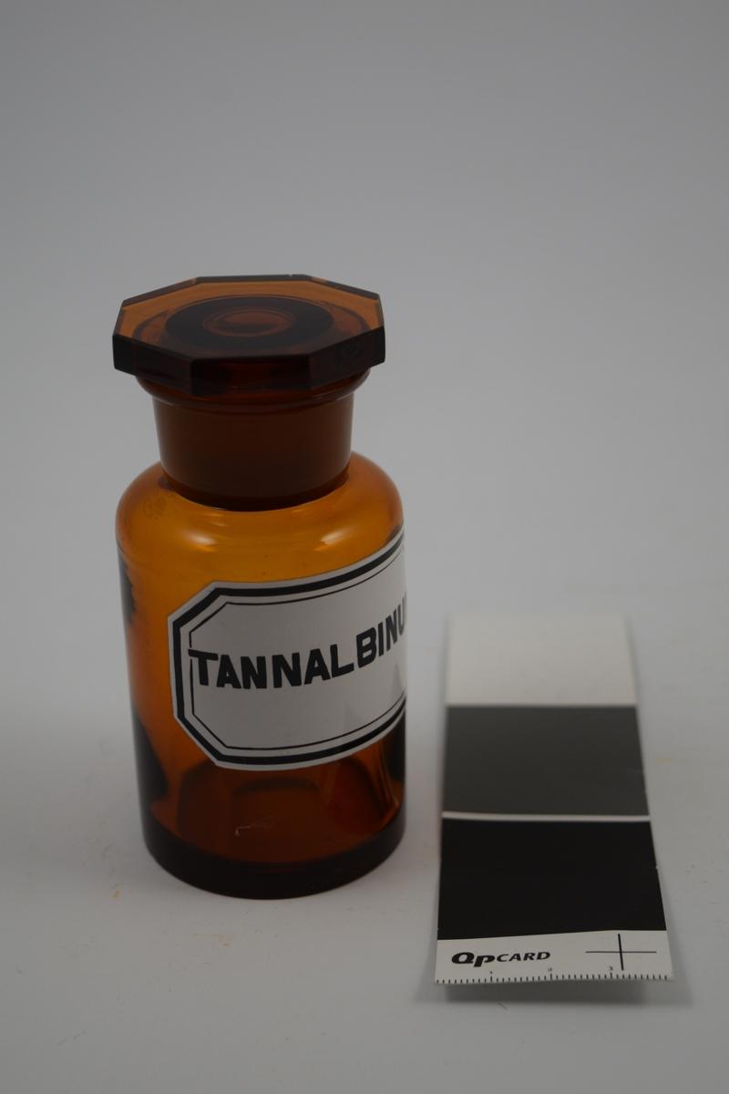 Brun glasskrukke med glasspropp. Hvit etikett med sort skrift. Har inneholdt Tannalbin, brukes mot diare.