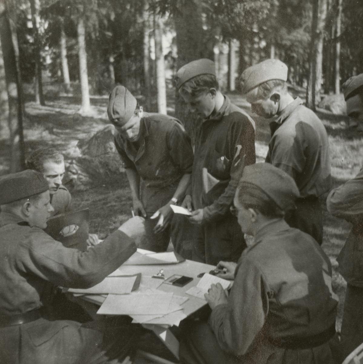 Soldater från Södermalands regemente I 10 samlade kring bordet.