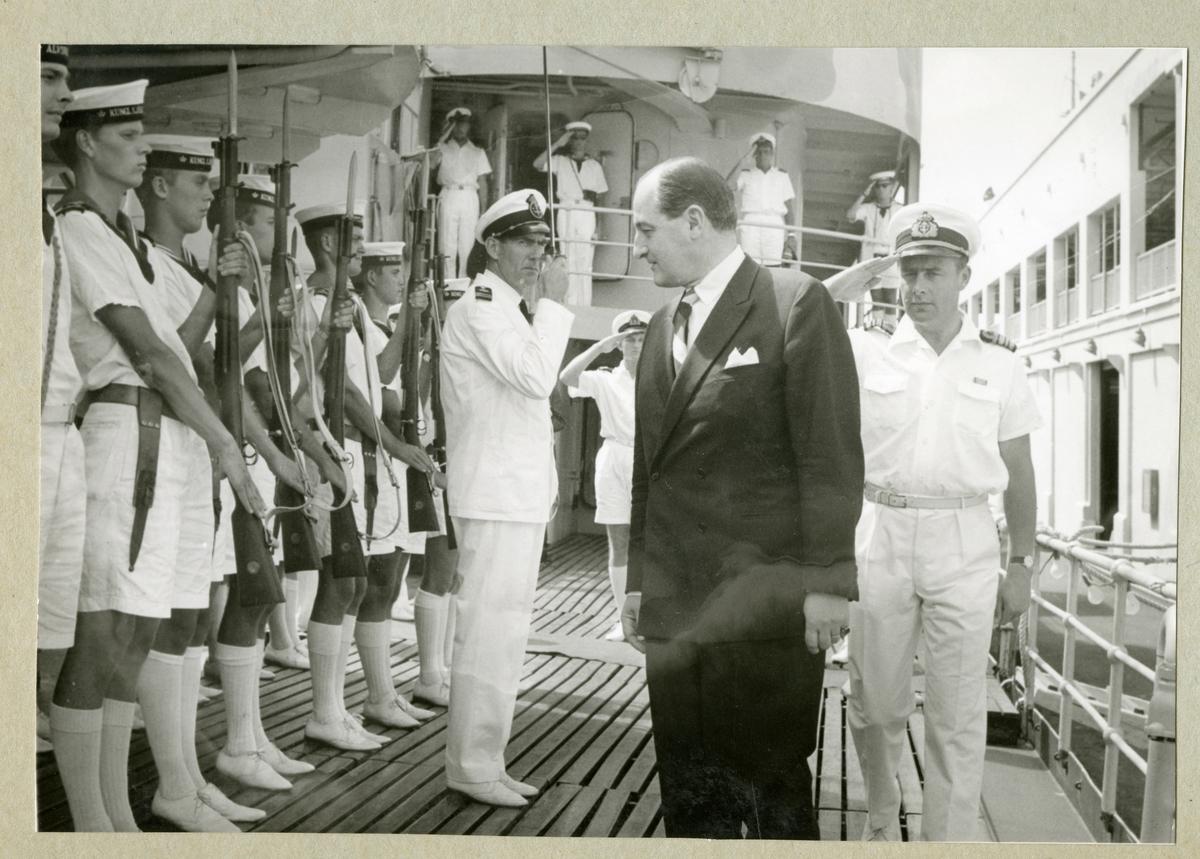 Bilden föreställer besättningsmän ombord på minfartyget Älvsnabben som är klädda i vita sommaruniformer och gör honnör eller står i givakt.  På bilden syns även en man i svart kostym. Bilden är tagen under fartygets långresa 1966-1967.
