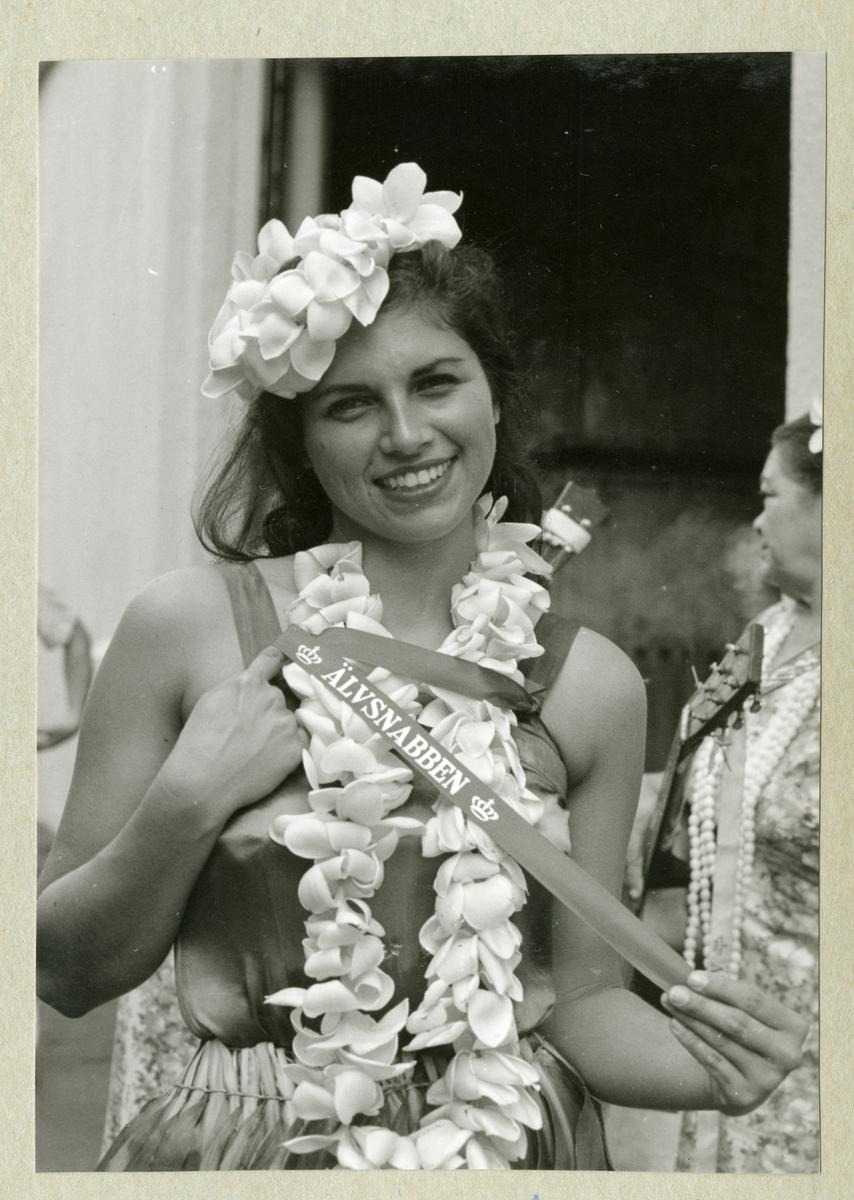 """Bilden föreställer en kvinna med bommor i håret och i en girlang runt halsen. I händerna håller hon ett band med texten """"ÄLVSNABBEN"""". Bilden är tagen under minfartyget Älvsnabbens långresa 1966-1967."""