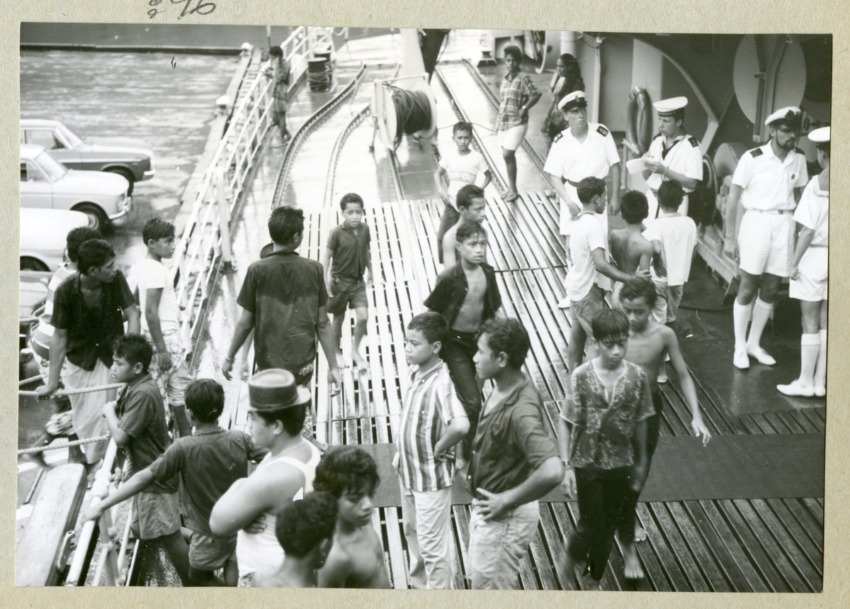 Bilden föreställer besättningsmän i vita sommaruniformer på minfartyget Älvsnabbens däck. På däck står även flera pojkar och män som är på besök på fartyget. Bilden är tagen i samband med långresan 1966-1967.