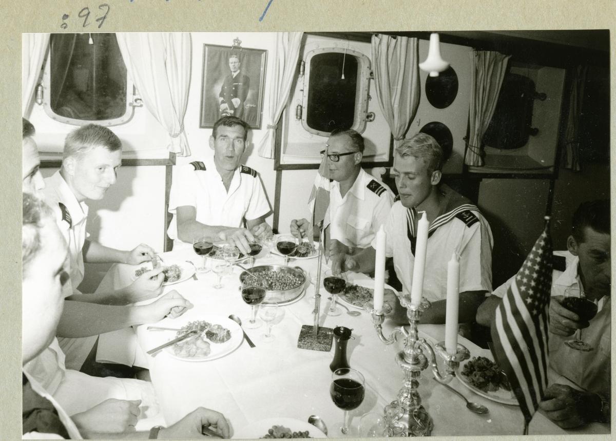 Bilden föreställer en middag i underofficersmässen med flaggstyrman Oskar Linde i fonden och med inbjudna gäster i form av ett antal officersaspiranter.