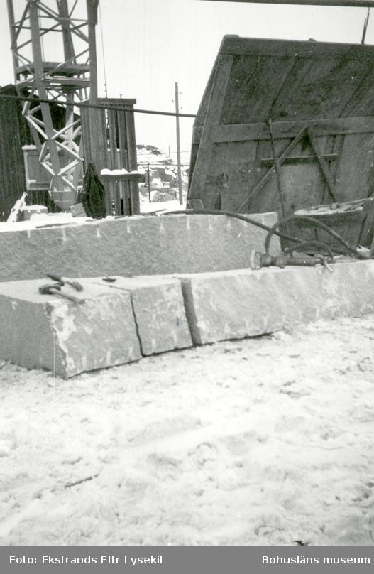 Stenblock och verktyg för stenbearbetning, i bakgunden hänger en kavaj