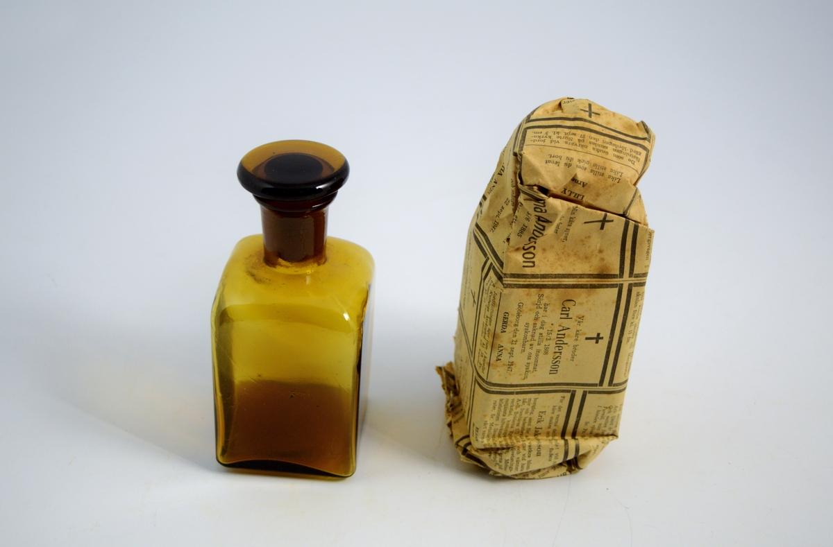 Brun firkantet standglass med glasspropp. Brukes til oppbevaring og salg av flytende.