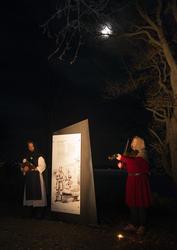 Munk i hvitt og svart synger mens mann i rød middelalderjakke og struthette spiller fiolin. Over lyser månen fra den mørke høsthimmelen. (Foto/Photo)