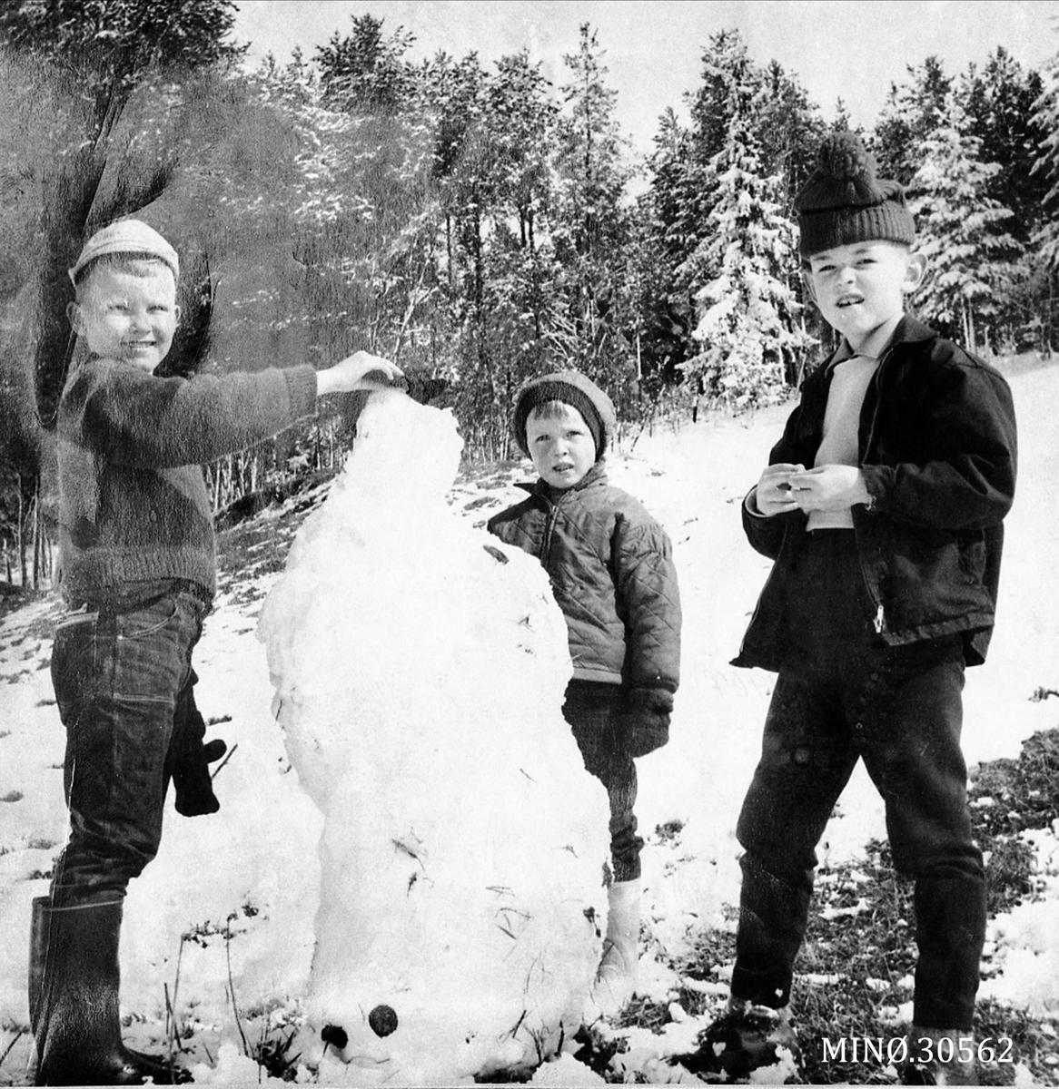 Tre barn som bygger snømann
