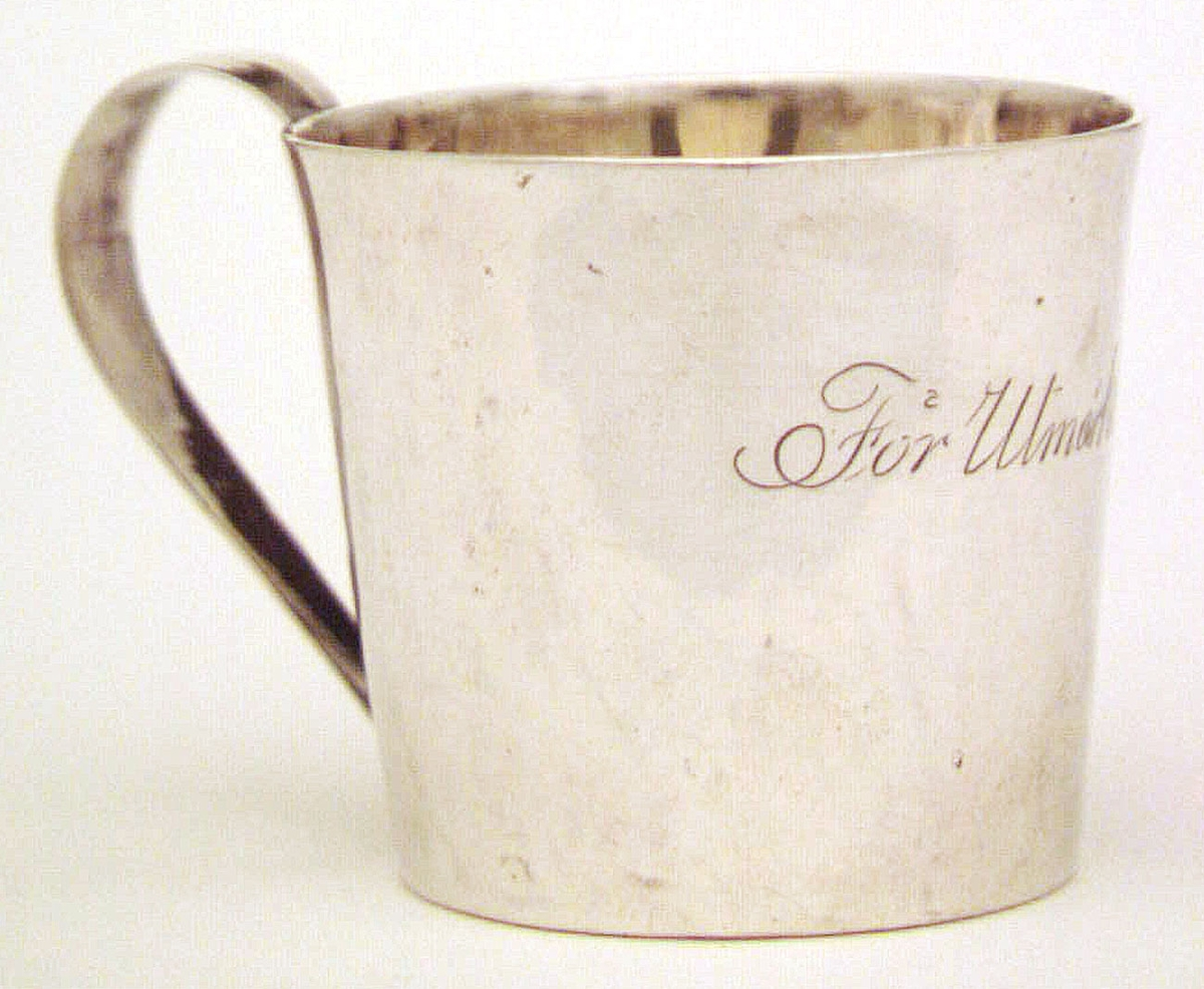 """Mugg med handtag. Text: """"För utmärkt flit"""". Ej identifierade stämplar i botten. Kattfot och årsbokstaven N3 1819."""