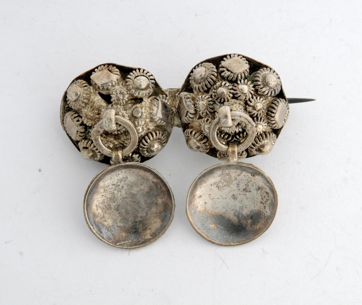 Sølje, halsknapp i sølv. Sett saman av to halvkuleforma knappar i filigransarbeid. Kvar knapp har hempe med ring og skål som vedheng. Nål og krok (i messing?) pålodda på baksida.