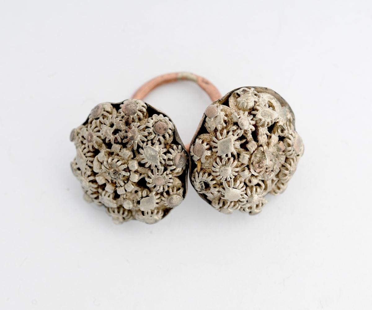 Sølje, halsknapp i sølv. Sett saman av to knappar i ein messing-ring. Kvar knapp er dekorert med filigransarbeid på framsida, glatt baksida i messing?