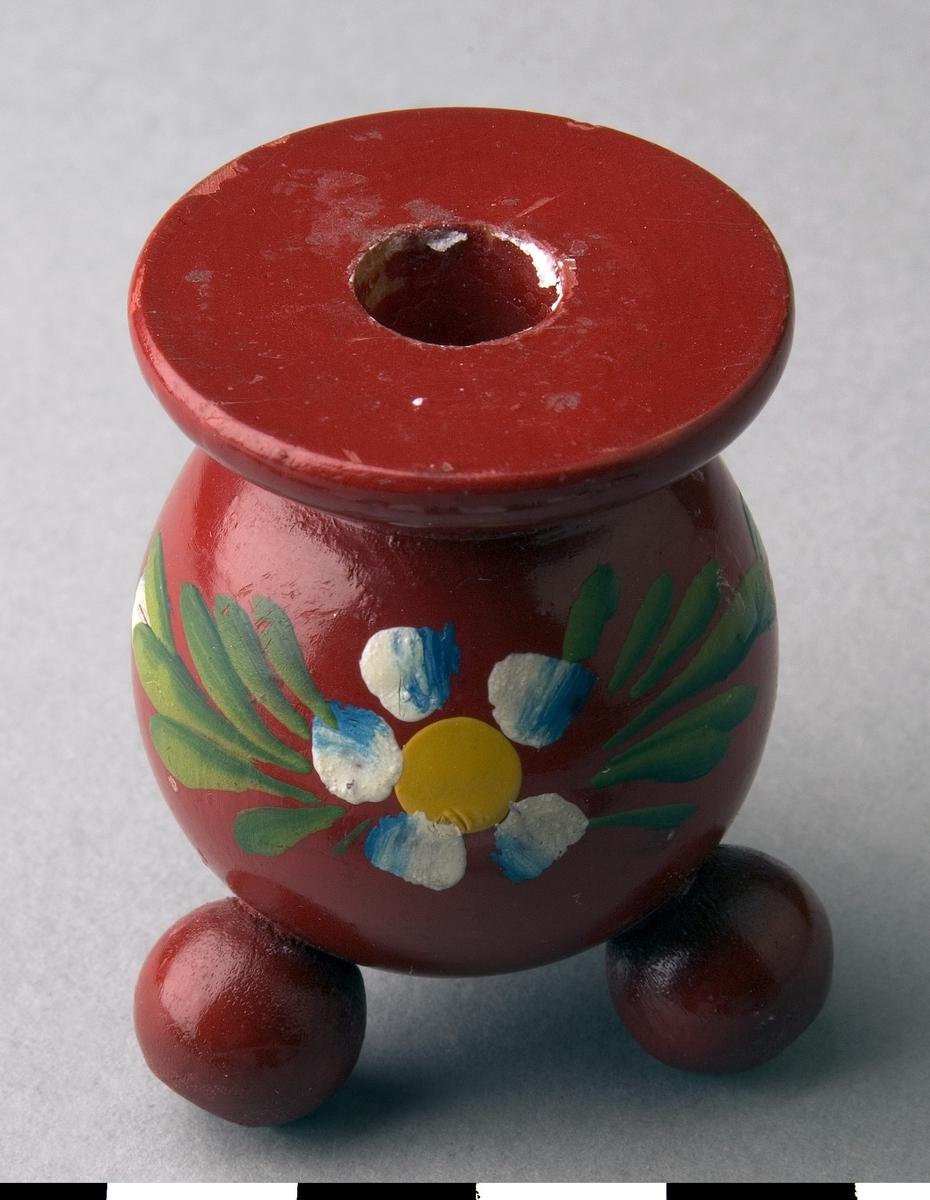 Kulljusstake av trä. Svarvad stor kula med ljushållare upptill, tre kulfötter. Målad i rött med litet blomster i vitt, blått, gult och grönt.
