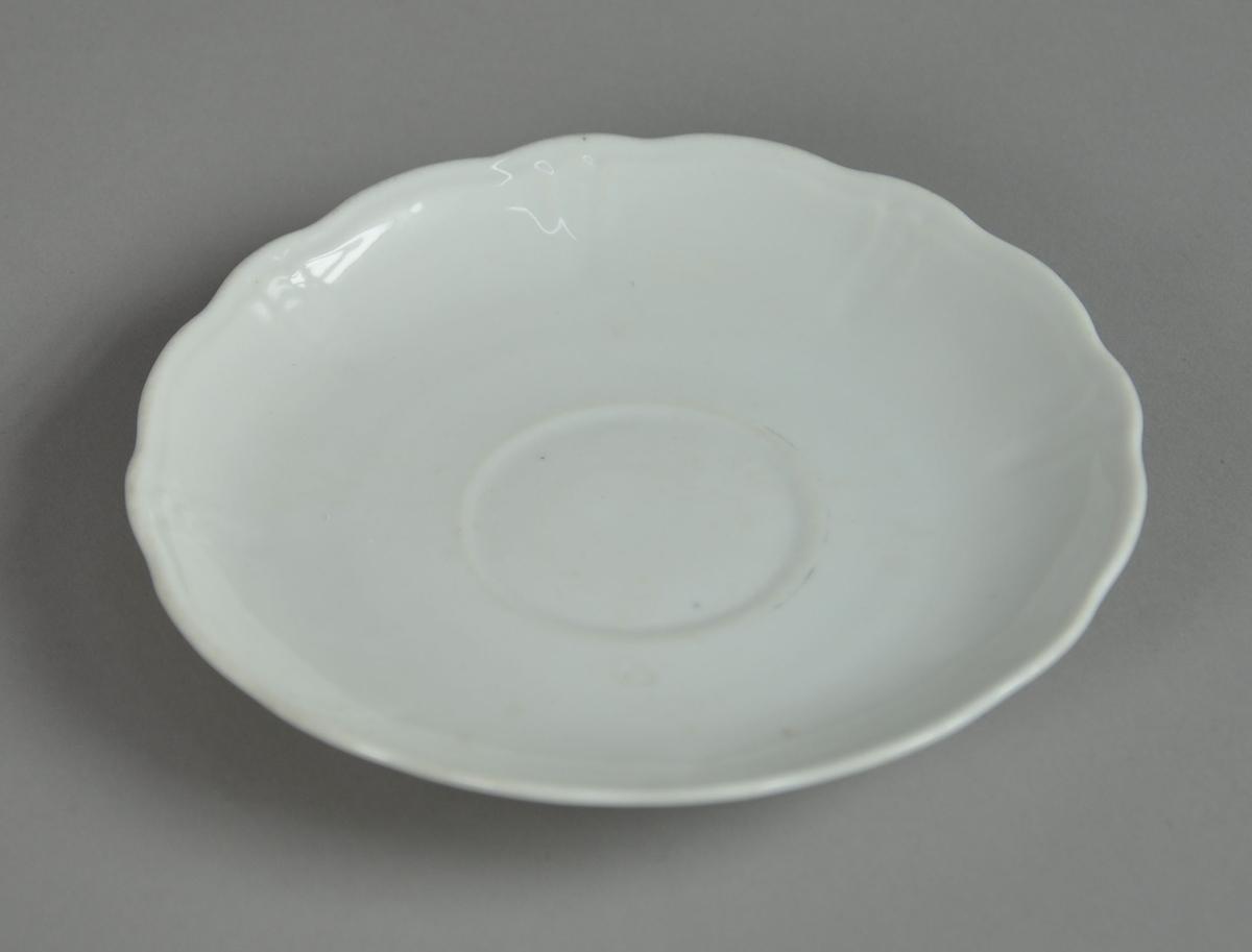 Koppeskål av glassert keramikk, med bølgete kant og preget dekor.