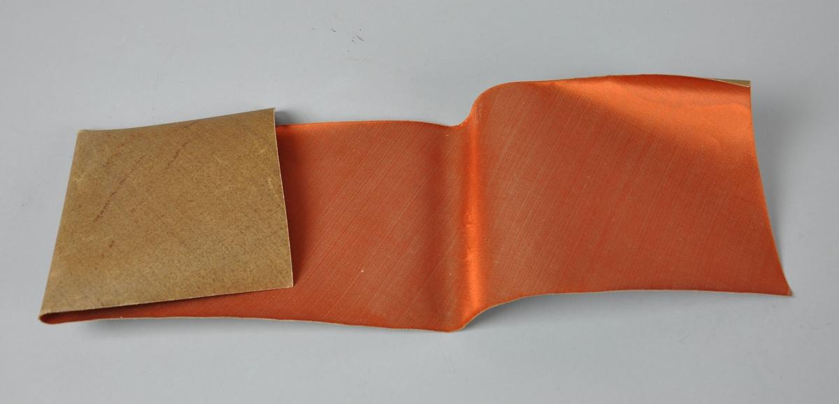 Rems med oransje silke til hatt. Stoffet bærer preg av bretting og bøying.