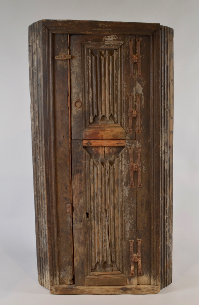 Kråskap av eik. Flat front, sidene skrånar inn mot veggen. To dører. Sidepanela og dørfyllingane har faldeverk. Profilert listverk rundt dørane og oppe og nede på skapet. To seinere påsette lister på nedste døra.