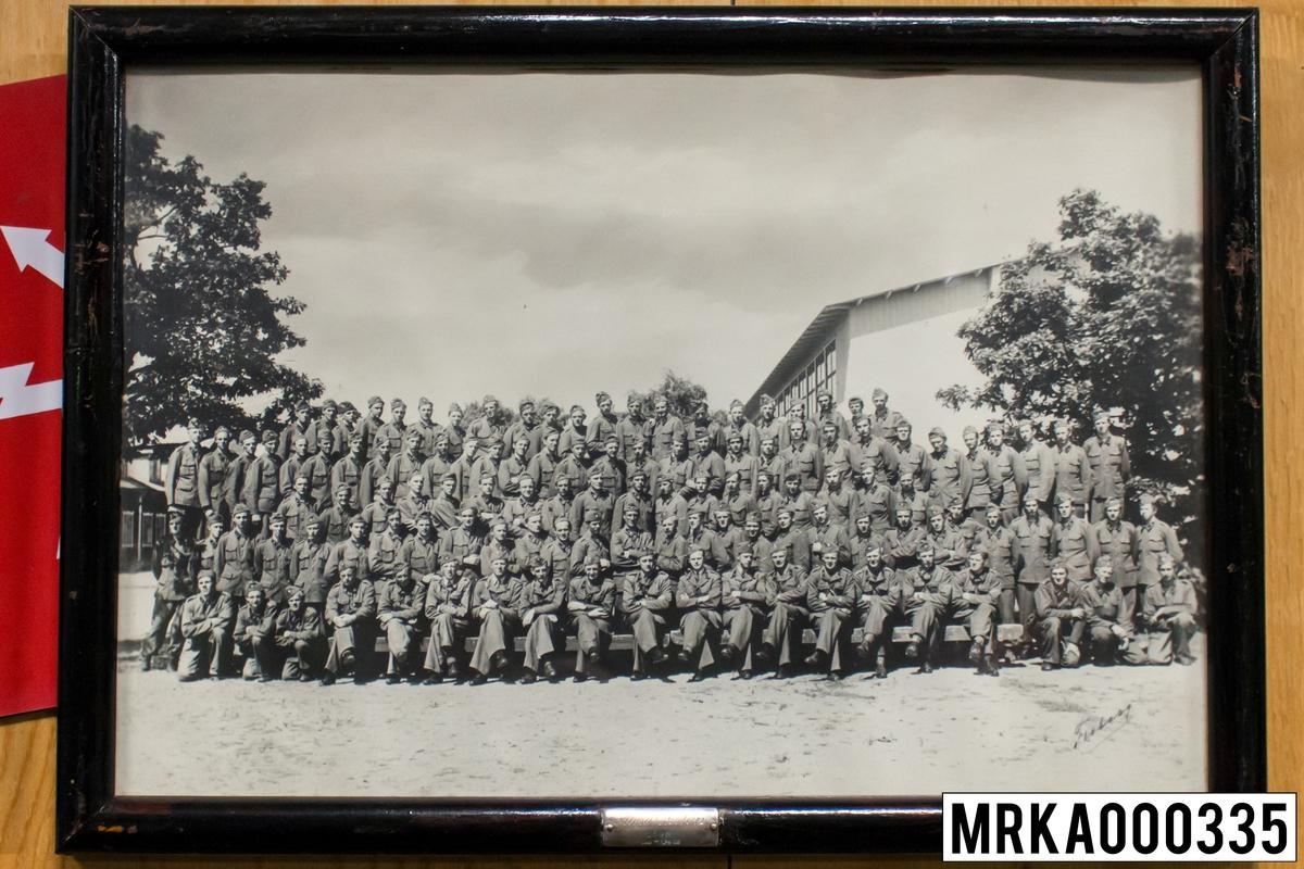 Fotografi taget på befäl och soldater som genomfört grundläggande soldatutbildning på 1:a Batteriet KA 2. Fotografiet taget på övre plan Gräsvik KA 2. Flobergs Foto 1946.