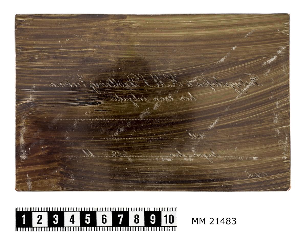 """Kliché bestående av rektangulär kopparplåt, liggande format. Graverad text. """"Fartygschefen å H.M.S. Drottning Victoria har äran inbjuda...till...dagen den...19...kl...O.S.A."""" Inslagen i papper försett med samma text. På baksidan skrivet med bläck: """"Denna plåt tillhör kvinnoförbundet för Sveriges sjöförsvar i Karlskrona."""", samt stämplat """"21 APR 1937""""."""