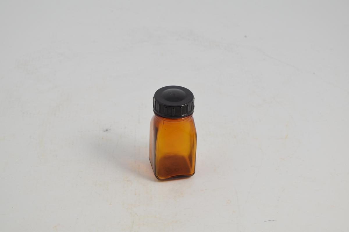 Brunt, transparent, firkantet glasskrukke med sort rund bakelitt lokk. Brukt til oppbevaring av tabletter i apotek og for salg.