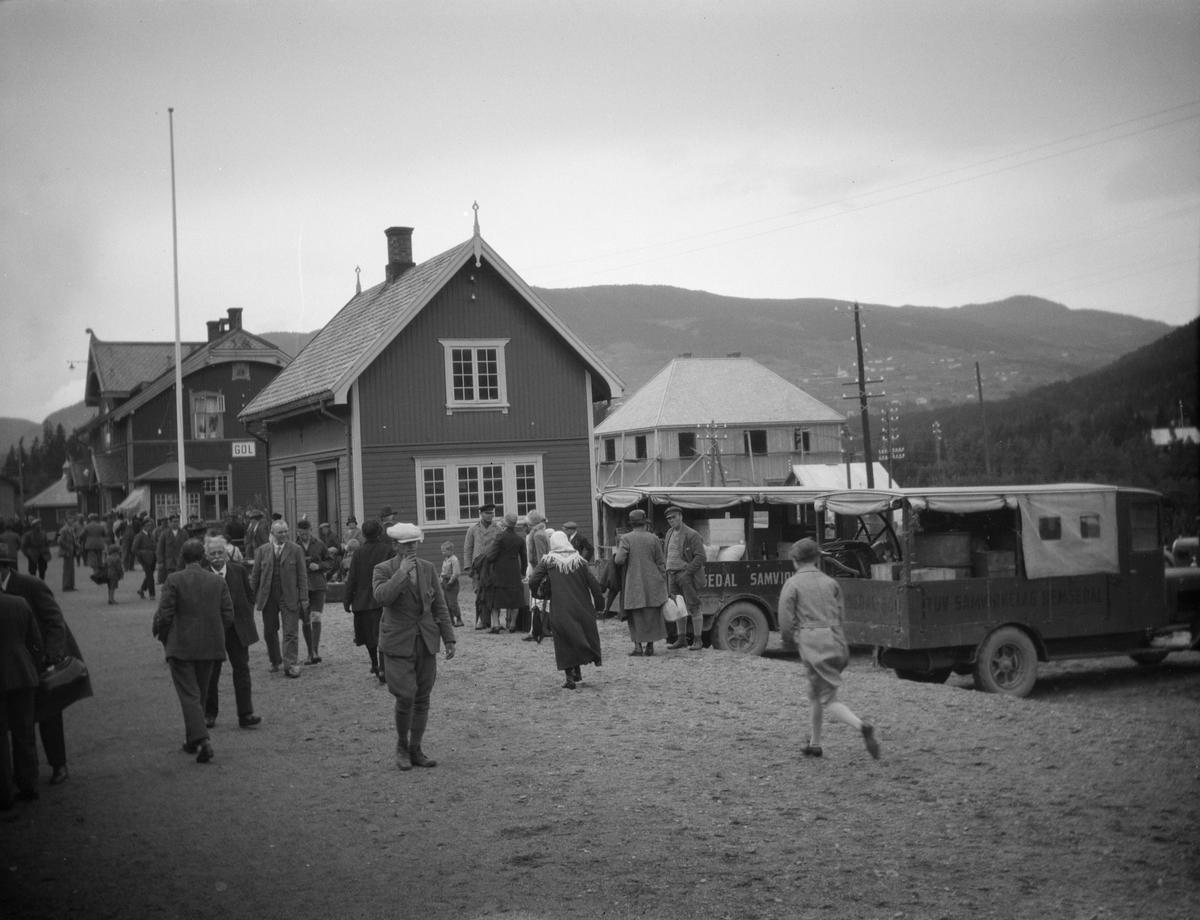 Folkemengde og lastebiler på Gol jernbanestasjon.