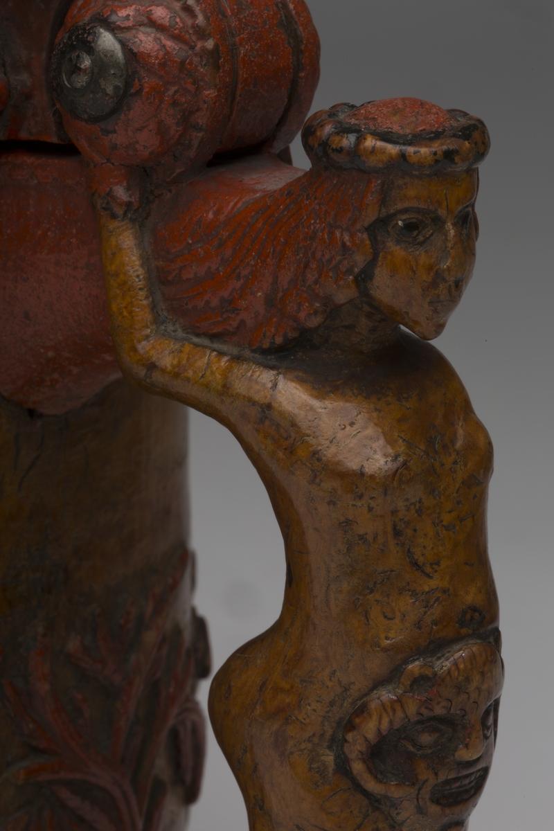 Dekorert med fortløpende billedfrise med dyr og trær på nederste del av korpus. Kannen har løveføtter og løvegjekk og bakkantine som håndtak.