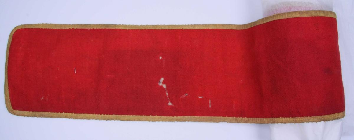 AV rødt ullstoff, skjøtt sammen av fem stykker. Linnen er kantet med gult silkebånd og fôret med tynt, åpent bomullstøy påtrykt streket rutemønster i brunsort med en rød og en brunsort blomst avvekslende i hver rute. Meget møllespist.
