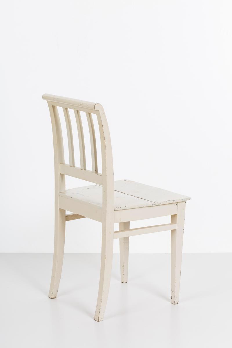 Hvitmalt spisestuestol. Sprosser i rygg og mellom stolbeina på venstre og høyre side.