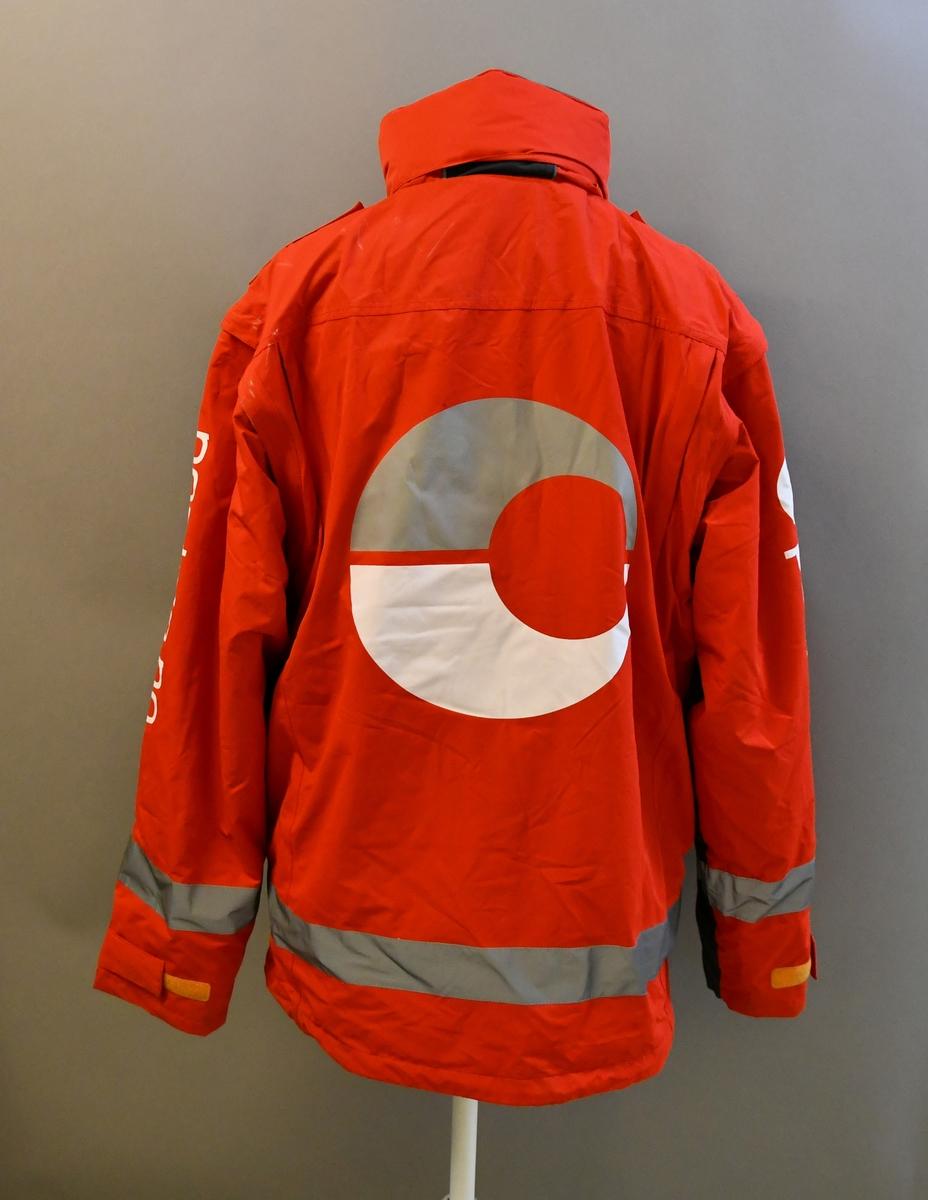 Rød uniformsjakke med tekst og posthornemblem. Med hette og avtagbart for. Med 4 lommer og mobillomme. Refleksbånd i livet og på ermene.  Størrelse XL