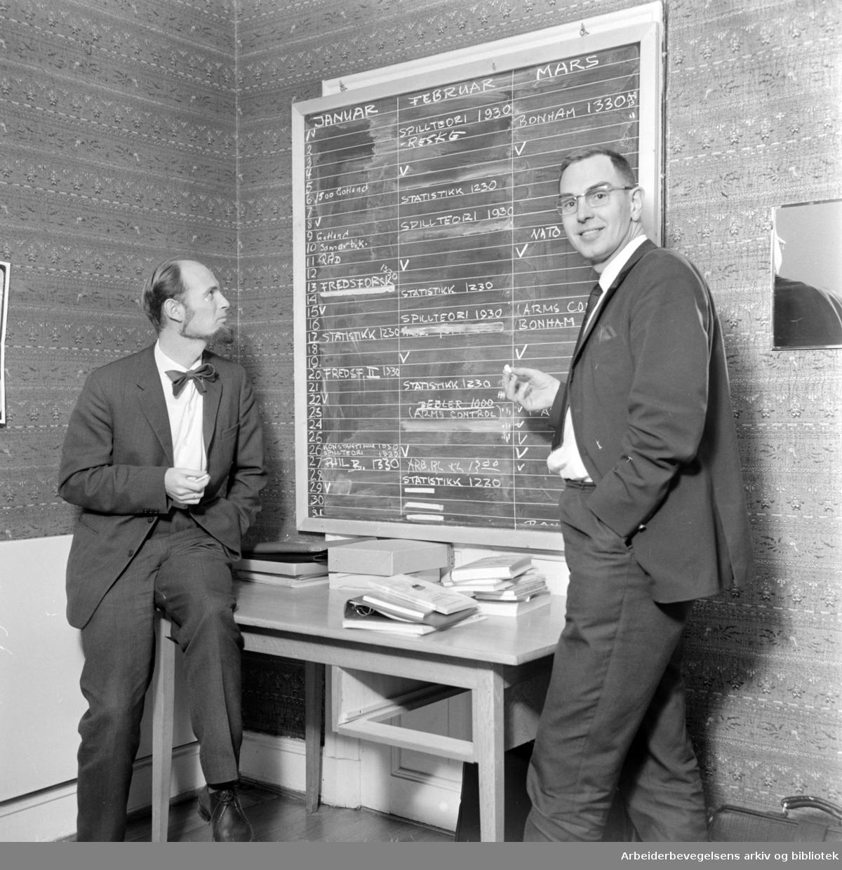 Utenrikspolitisk institutt i Parkveien. Olav Stokke og Per Frydenberg studerer tavlen, som forteller om dagsprogrammene ved Instituttet. Mars 1967