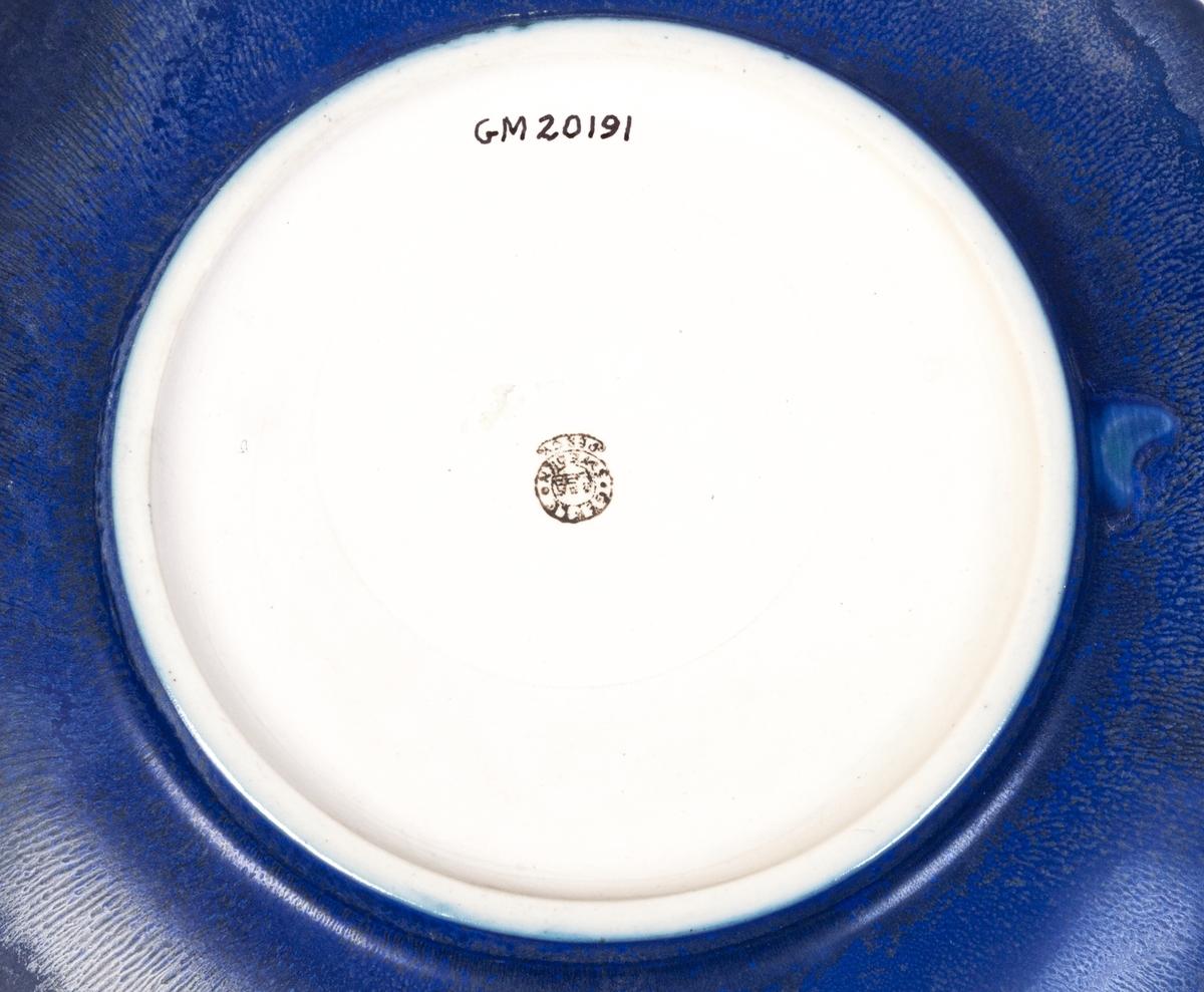 """Fat av stengods, förmodligen fruktfat, formgivet av Arthur Percy för Gefle Porslinsfabrik, okänd modell. Original. Runt med upphöjd spegelkant. Ytterkant slät. Stor, rund fotring. Dekor, glasyr 30, blåklintsblå med effekter. Svart skorstensstämpel under med text """"Gefle Sweden Percy""""."""