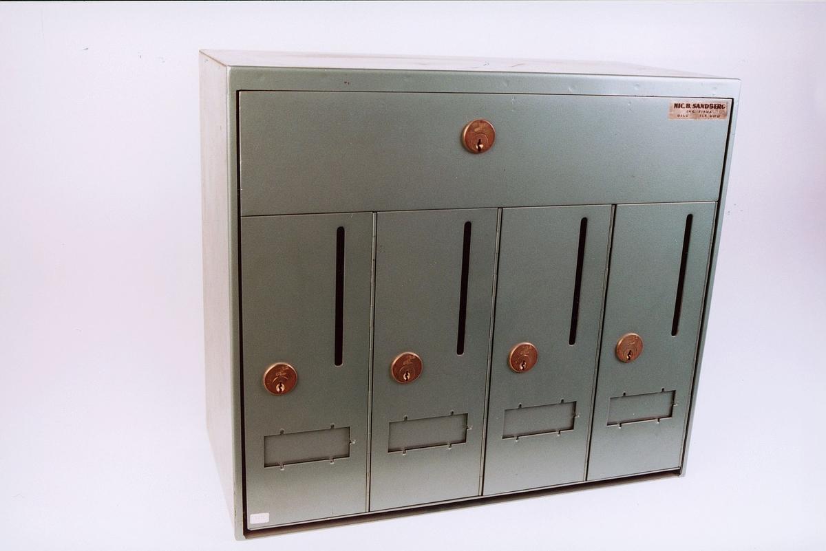 Anlegg for levering av post i blokkbebyggelse. 4 låsbare brevkasser og låstbart lokk for postbudet.