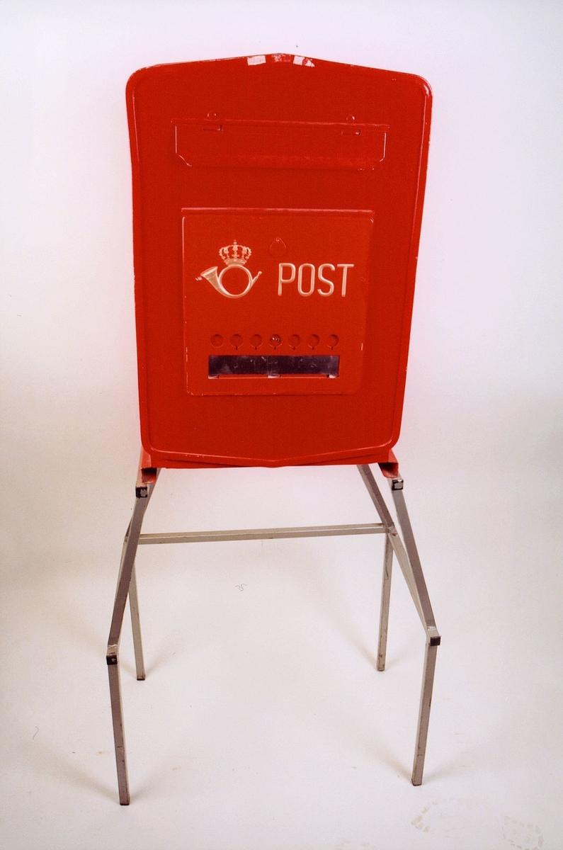 Rød mekanisk tømmepostkasse for tømmeapparat. Med posthornemblem og ordet Post i gul skrift. Felt med tømmetider og markering av når tømt.