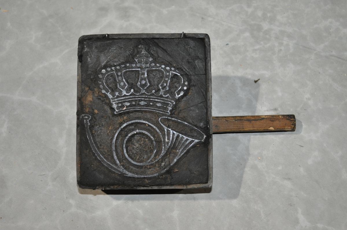 Klisjeen ligger i en metallramme. Bunn av tre og trehåndtak.