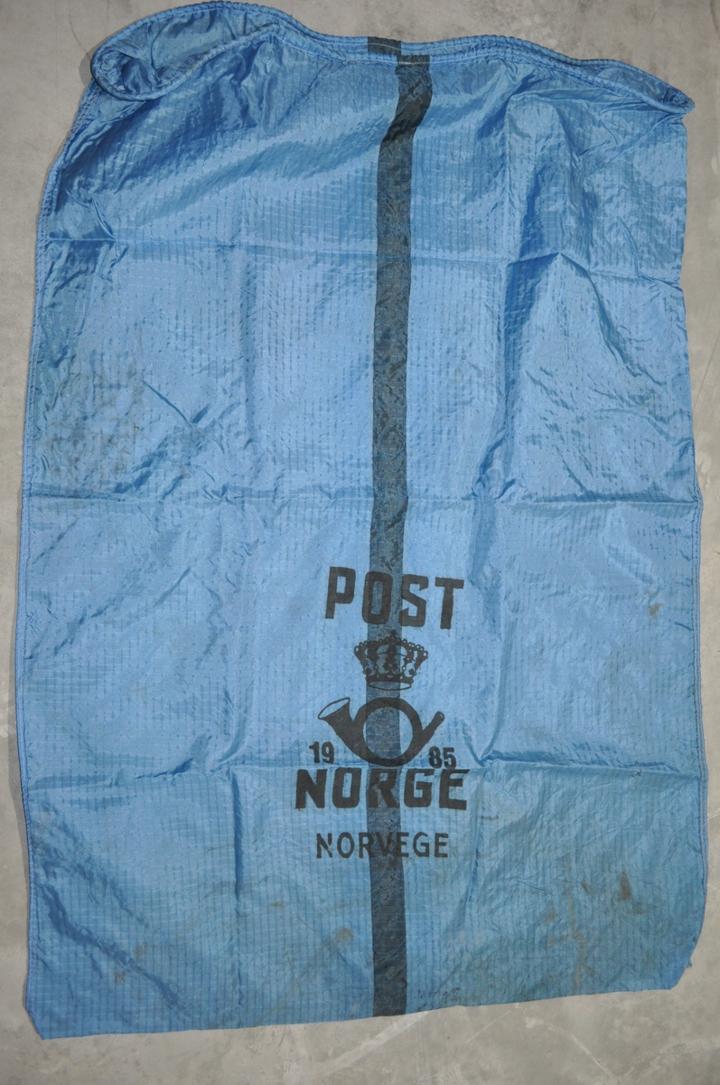 Blå postsekk med postlogo og årstall. Postsekken har en svart stripe på midten.