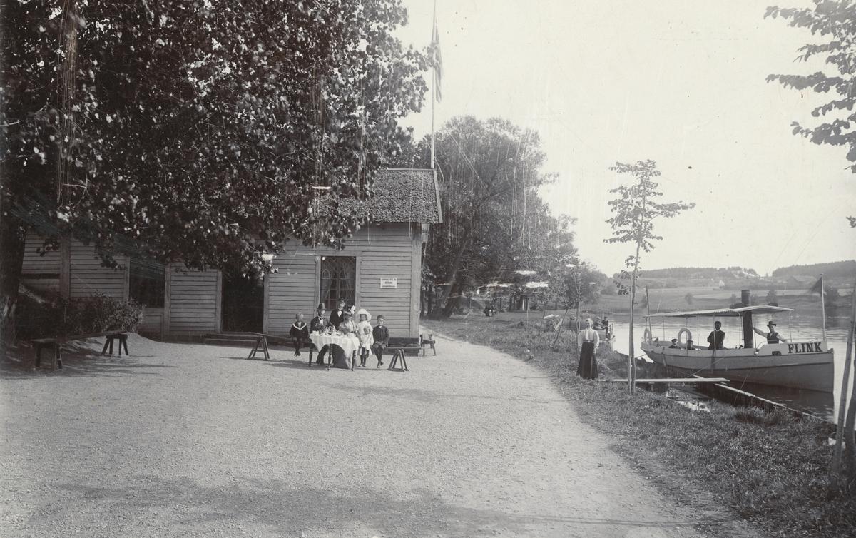 Repigt men unikt motiv från Ladugårdskällans servering i Linköping. Enligt påskrift sitter familjen Carlsson vid kaffebordet. Till höger ångslupen Flink, som vid tiden gick passagerartrafik mellan Nykvarn och Tannefors.