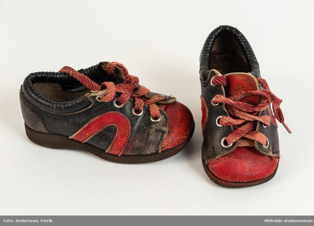 """1 par skor i storlek 23, från 1975. Skon är brun och röd. Skosnöret är brun och röd randigt.   Inuti skon finns stämpeln: """"Friskus! Pax, Rex, Master"""", men är något slitet. I sulan finns """"23 A"""" inristat."""