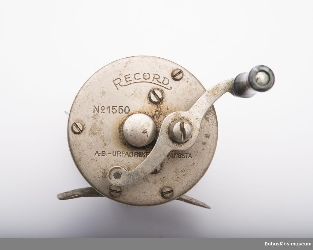 """Skall fästas på ett spinnspö. Två runda metallplattor vilka är sammansatta parallellt på 4,5 cm avstånd med fem stycken metallstavar. På den ena staven är det en an- ordning som får fisklinan att fördelas jämt på rullen. Vev på ena sidan med ett litet handtag i svart- och gråmelerad ureaplats. Ursprungligen har det varit två handtag. Text på den ena metallplattan:""""RECORD NO 1550 A.-B. -URFABRIKEN - SVÄNGSTA"""". På den andra plattan är det ristat:""""Bertil Becker"""" samt något oläsligt. Blå lina av polyamidfiber upplindad på rullen. Metallplattan undertill vilket är en fästanordning för att få fast rullen vid ett spö. På plattan står det:""""MADE IN SWEDEN"""". Linan är troligen från 1950-talet."""