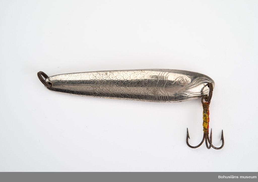 Fiskliknande pilk med fiskfjällsmönster. Försedd med trekrok, vars skaft omlindats med gult och rött garn för att locka fisken. Garnet delvis bortslitet.