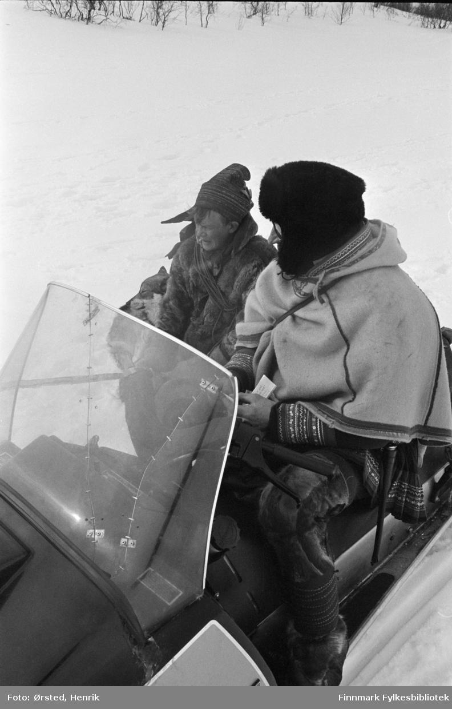 """Postfører Mathis Mathisen Buljo, bedre kjent som """"Post-Mathis"""" i samiske kretser, i samtale med en reindriftssame ute på vidda.  Fotograf Henrik Ørsteds bilder er tatt langs den 30 mil lange postruta som strakk seg fra Mieronjavre poståpneri til Náhpolsáiva, videre til Bavtajohka, innover til øvre Anárjohka nasjonalpark som grenser til Finland – og ruta dekket nærmere 30 reindriftsenheter. Ørsted fulgte «Post-Mathis», Mathis Mathisen Buljo som dekket et imponerende område med omtrent 30.000 dyr og reingjetere som stadig var ute i terrenget og i forflytning. Dette var landets lengste postrute og postlevering under krevende vær- og føreforhold var beregnet til 2 dager. Bildene gir et unikt innblikk i samisk reindriftskultur på 1970-tallet. Fotograf Henrik Ørsted har donert ca. 1800 negativer og lysbilder til Finnmark Fylkesbibliotek i 2010."""