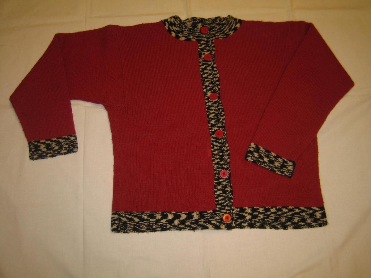 Kofta Stickad i rätstickning i rött med muddar, halskant, knappkant och nederkant i svartvitt flamgarn. Yttersta varven på dessa är mossstickade med fyra varv. Det är sex röda knappar i knappraden.