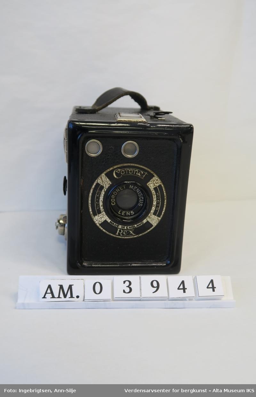 Kamera, eller kasseapparat, med hele mekanismen lukket i en rektangulær kasse. Frontdel og omramming av bakside i lakkert stål, kassen ellers trukket med skai.