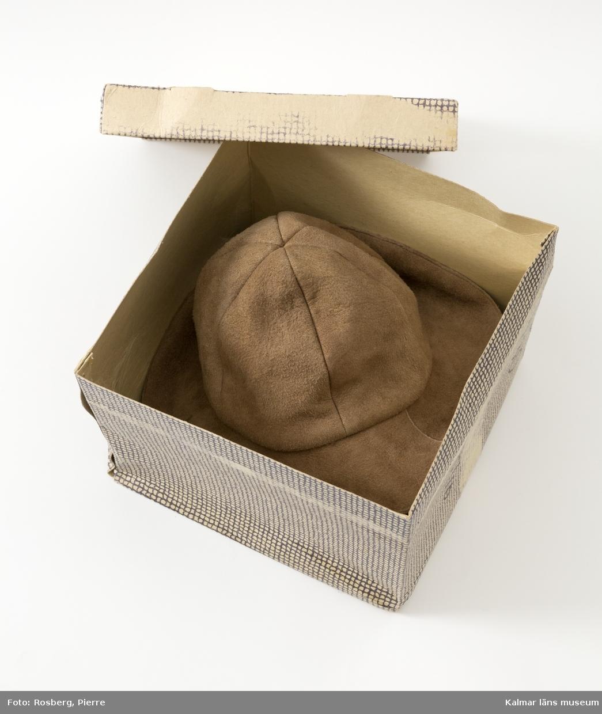 """KLM 45621:3:2. Hattask. Av papp. Kubformad med avtagbart lock. Tryckt rutmönster i grått på hattaskens utsidor. Sammanfogad i två av hörnen med vitmetallklammrar. Sättet hattasken är ihopvikt på i botten bildar en kulle, av fyra """"flikar"""" invändigt i asken. Stängs med snöre av växtfibrer. På locket två st. påklistrade etiketter. Mindre vit etikett med tryckt svart text: 230 Mörbylånga. Större vit etikett med förtryckt svart text, maskinskriven text samt handskriven text med blå kulspetspenna: Herdepälsen, 380 62 Mörbylånga, mm. På askens ena sida är skrivet med svart tuschpenna: 230 5/10. Hatt KLM 45621:3:1 förvarades i hattasken."""