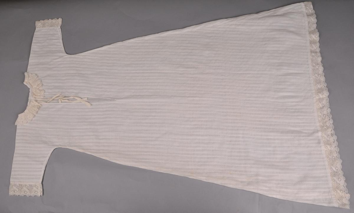 Kvit kjole av mønstervove bomullstoff ( myggtjeld ). Kniplingsblonde av bomull framme på arm, nede på kjolen og foldelagt rundt hals. Kjolen har eit enkelt snitt med lange armar, er heilklypt og utskrådd med innfelde kilar nede, saum i sidene, splitt midt bak og to par kvite bendelband til knyting. Maskinsaum og handsaum.