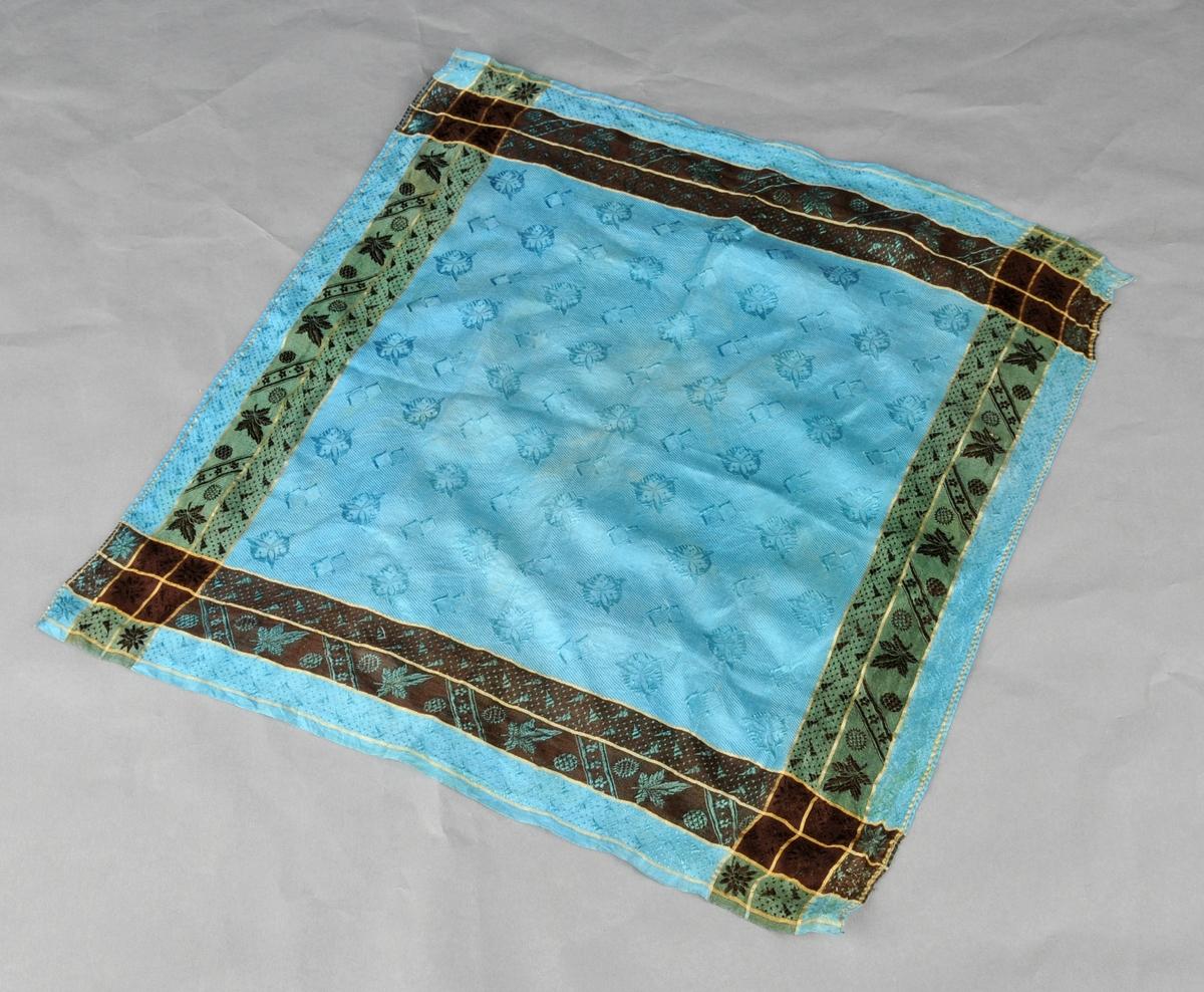 Silketørkle med blå botn. Blomstrete mønster med striper i gult, grønt og svart langs kanten.