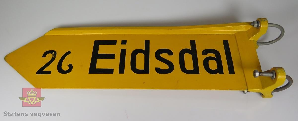 """Vegviser med plate av aluminium, spisset i enden. Festet og øvre kant støpt i en del. Svart skrift """"26 Eidsdal"""" på gul bunn. Teksten """" 24 Rørvik"""" er skjult under fargen. 3"""" klemmer for skiltstolpe."""