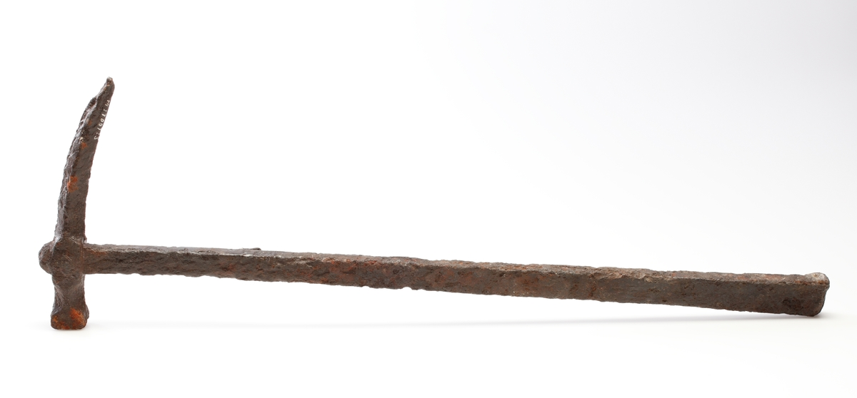 Stridshammare med ca 2 x 2 cm stor kvadratisk nacke och genom urskärningar profilerad hals. Avslutas i en lång, böjd spets med rombiskt tvärsnitt. Hammaren fäster i skaftet med en tvärgående nit, som också håller en ten för fastsättning i bältet på ena sidan. Skaftet är rektangulärt, bredast nedtill och rundhamrat upptill.