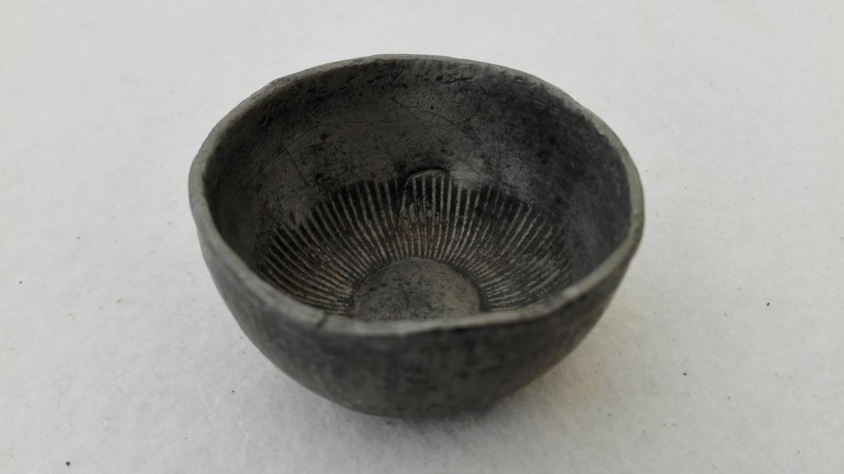 1 tomling av tin.  Tomling stöpt av tin med forsiringer (stöpte) saavel utenpaa som indvendig.  Kjöpt av Jens Simonsen, Sogndal.