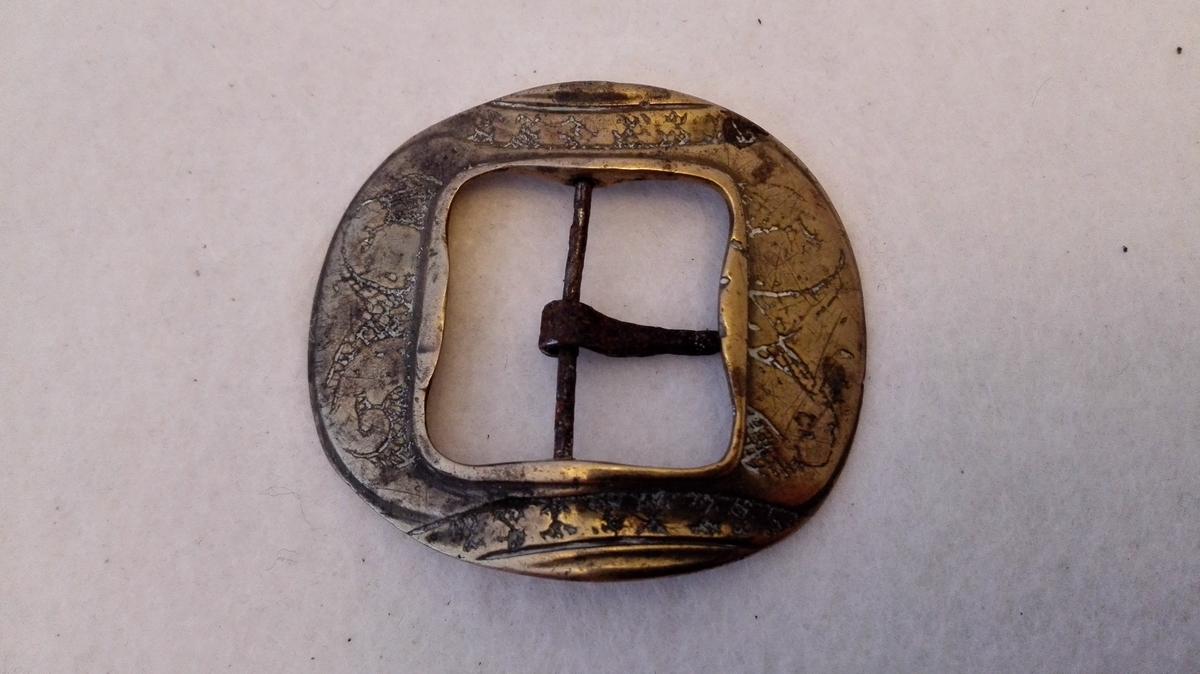 1 messing skospænde.  Liten stöpt messing skospænde paa hvis overside indgraverte ornamenter. Fra Lærdal.  Samtlige disse gjenstander (11643 - 53) Kjöpt ved Kjöbmand Th. Lindström, Lærdal.
