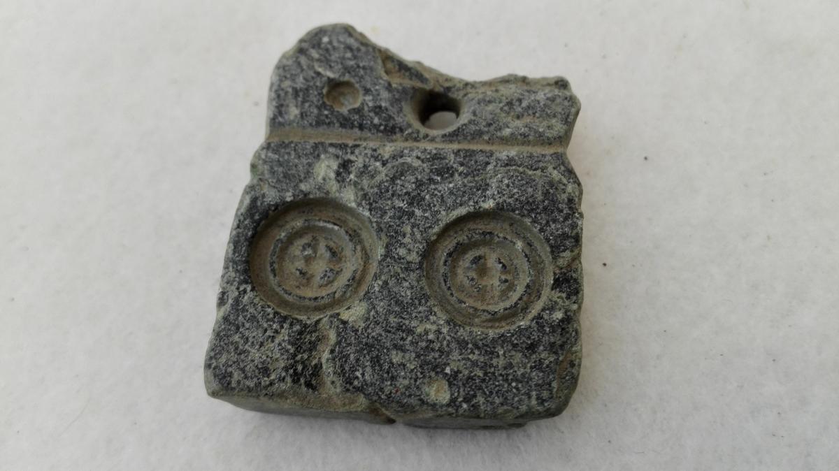 1 Stöpeform av Klæbersten  Liten firkantet 0,8 cm tyk klæberstensplate med hul i den ene kant.  I platen på den ene side inngravet form for to knapper, på den anden for en knapp, alle av samme type. Fundet i en aker på Aarvold i Sogndal.  Gave fra frk. Ida Troge, Sogndal
