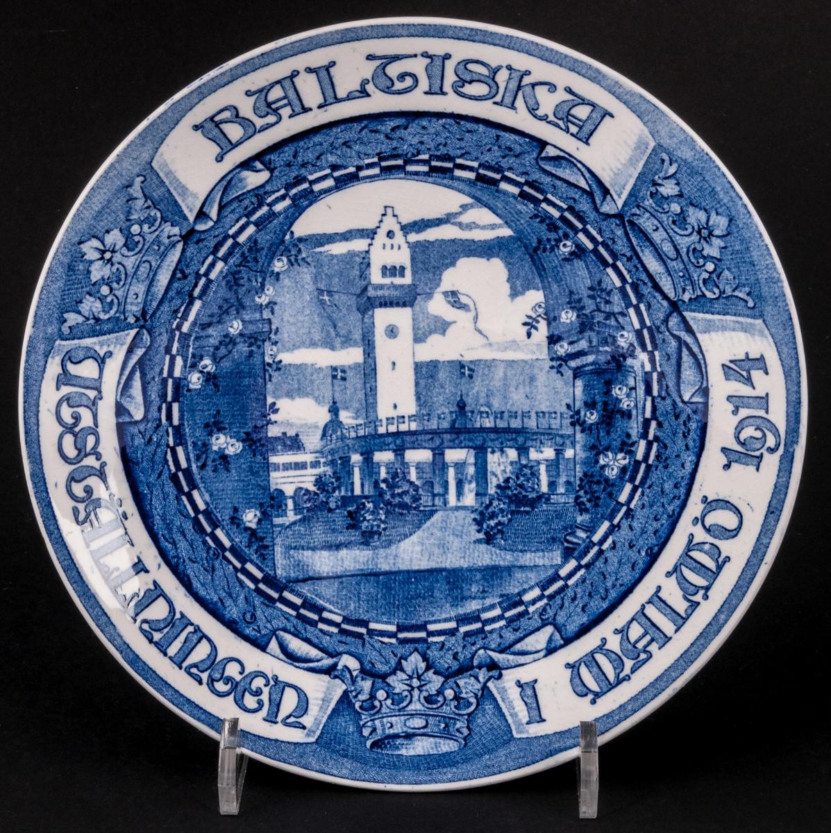 Jubileumstallrik i lergods, för Baltiska utställningen i Malmö 1914. Vit med blå text och motiv. Modell L. Tillverkad vid Gefle Porslinsfabrik. Försedd med hål och upphängningssnöre.